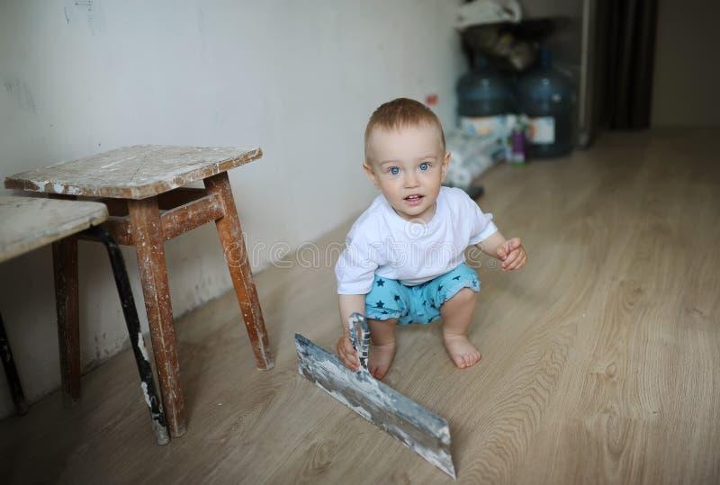 A criança guarda à disposição a espátula do cimento foto de stock