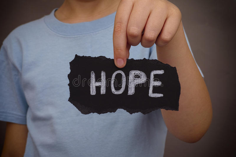 A criança guarda a parte de papel preto com esperança da palavra foto de stock