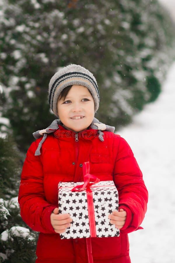 A criança guarda um presente do ano novo do xmas em suas mãos imagem de stock