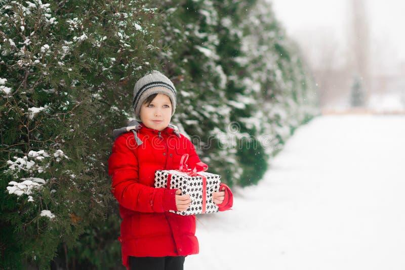 A criança guarda um presente do ano novo do xmas em suas mãos fotografia de stock royalty free