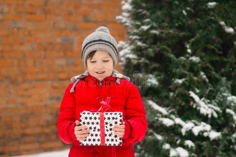A criança guarda um presente do ano novo do xmas em suas mãos imagens de stock royalty free