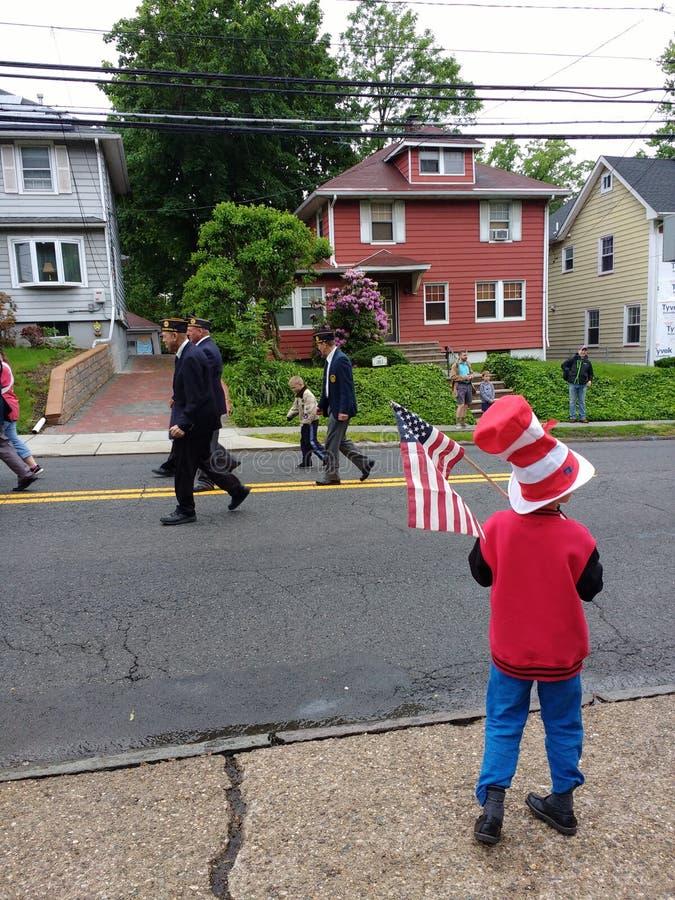 A criança guarda uma bandeira americana, parada de Memorial Day, EUA imagem de stock