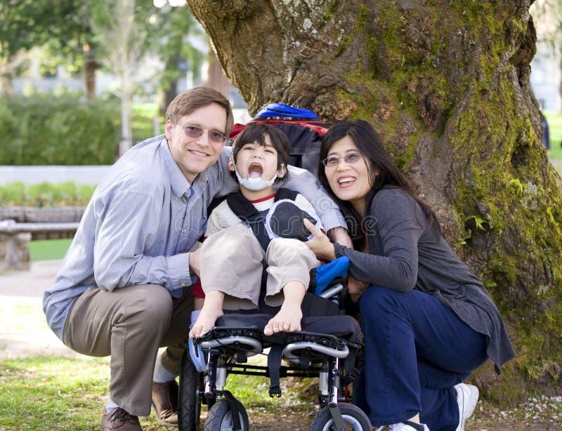 Criança incapacitada cercada por pais foto de stock