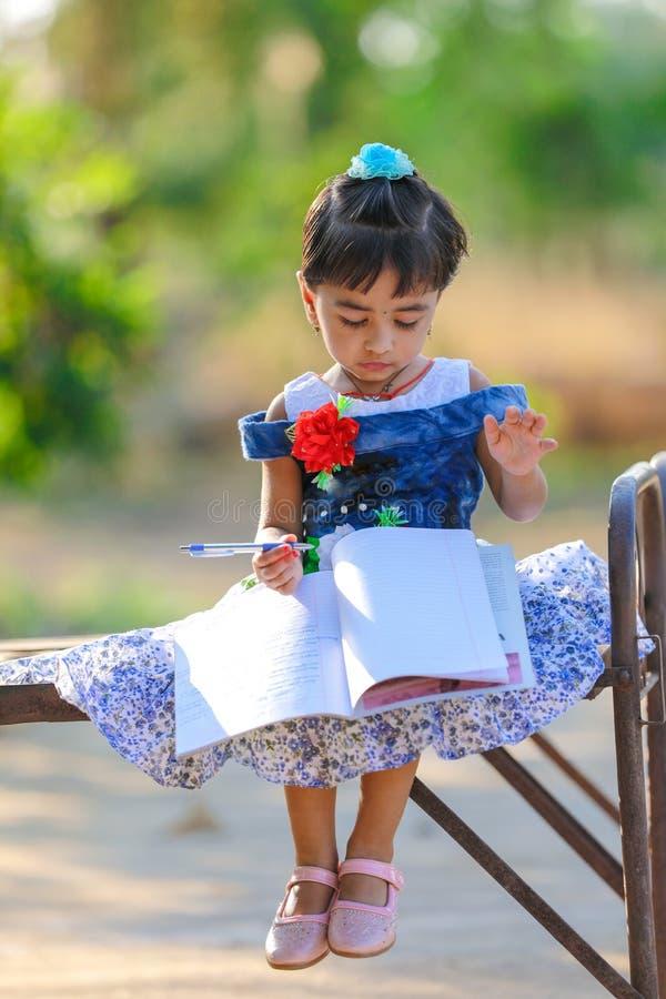 Criança indiana da menina que escreve no livro de nota, estudando fotos de stock