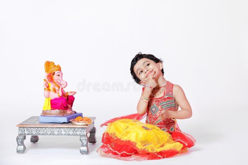 Criança indiana pequena da menina com ganesha e rezar do senhor, festival indiano do ganesh fotos de stock royalty free