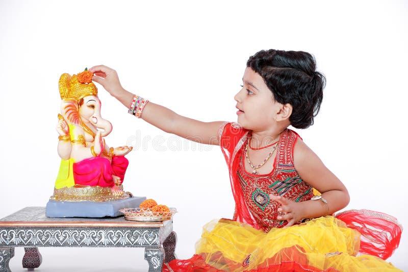 Criança indiana pequena da menina com ganesha e rezar do senhor, festival indiano do ganesh foto de stock