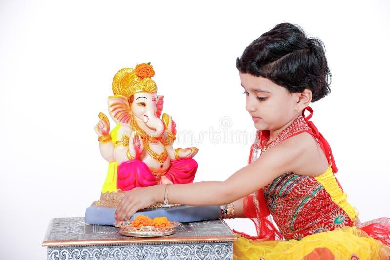 Criança indiana pequena da menina com ganesha e rezar do senhor, festival indiano do ganesh foto de stock royalty free