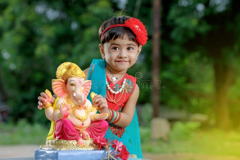 Criança indiana pequena da menina com ganesha e rezar do senhor, festival indiano do ganesh fotos de stock