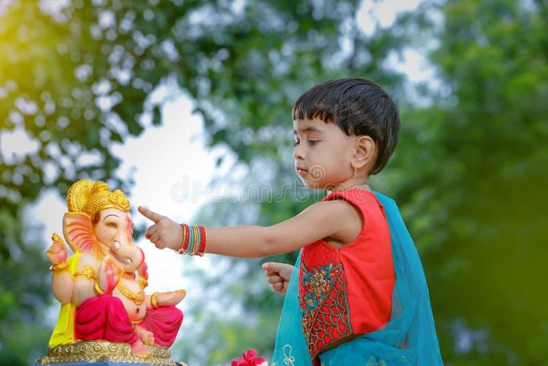 Criança indiana pequena da menina com ganesha e rezar do senhor, festival indiano do ganesh fotografia de stock royalty free