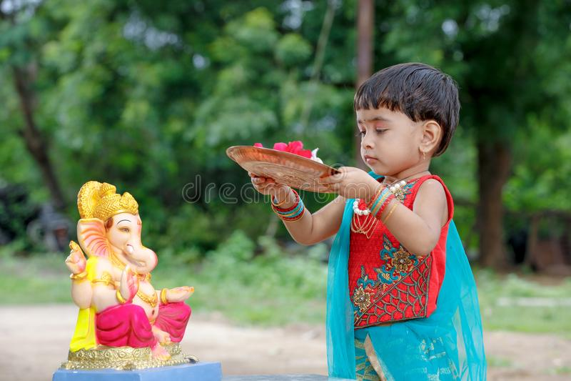 Criança indiana pequena da menina com ganesha e rezar do senhor, festival indiano do ganesh fotografia de stock