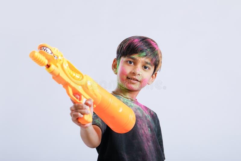 Criança indiana que joga o holi com arma da cor imagem de stock royalty free