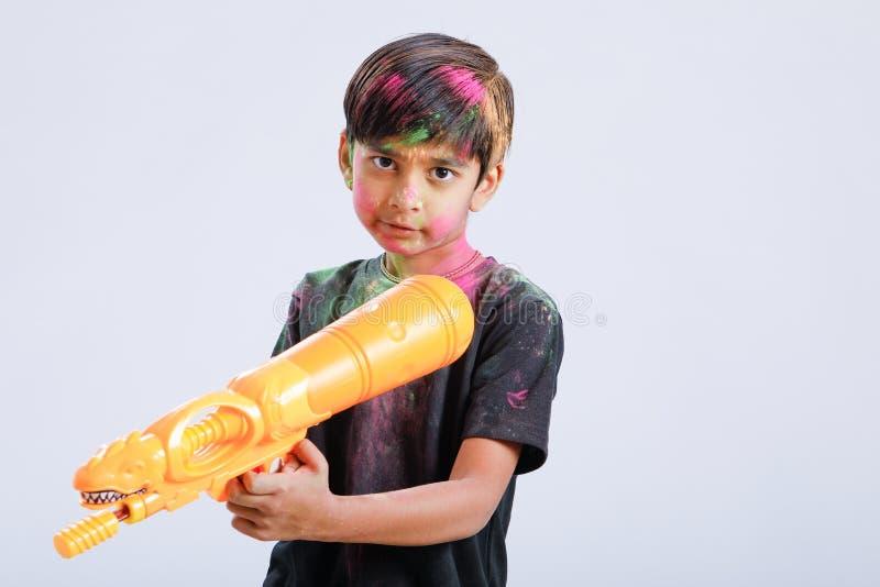Criança indiana que joga o holi com arma da cor fotos de stock royalty free