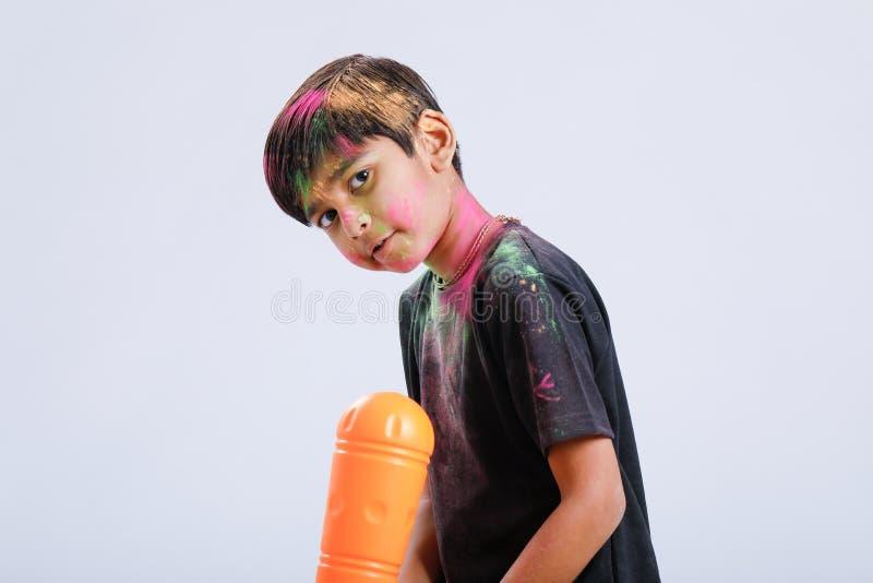 Criança indiana que joga o holi com arma da cor imagem de stock