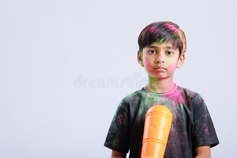 Criança indiana que joga o holi com arma da cor fotos de stock
