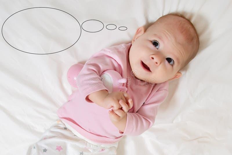 Criança infantil feliz do bebê que imagina algo e o sorriso imagens de stock royalty free