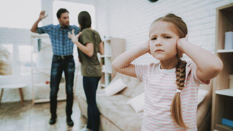 A criança infeliz da discussão dos pais fecha as orelhas na casa imagem de stock royalty free