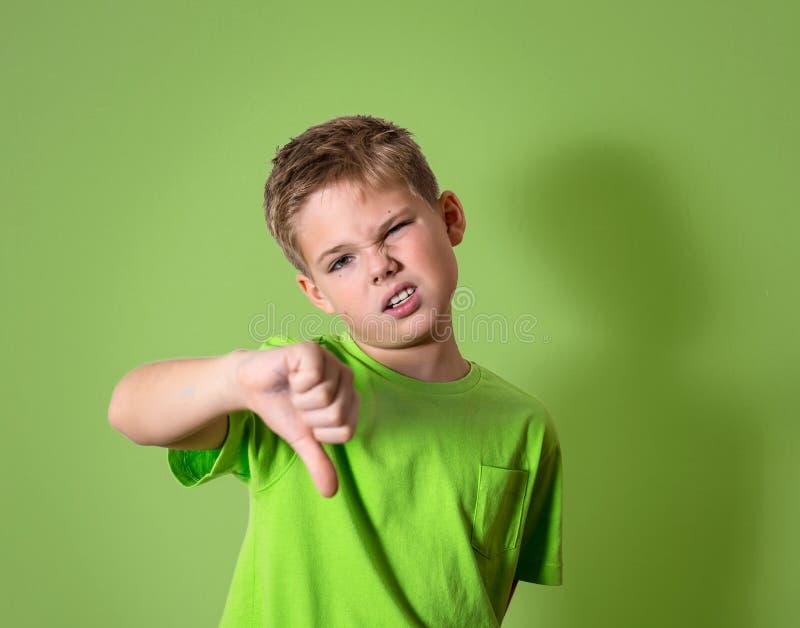 Criança infeliz, irritada, desagradada que dá o gesto de mão dos polegares para baixo, isolado no fundo verde fotografia de stock royalty free
