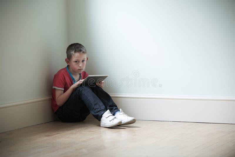 Criança infeliz que senta-se na sala com tabuleta de Digitas imagem de stock royalty free