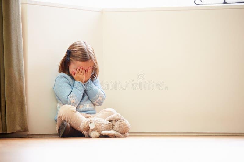 Criança infeliz que senta-se no assoalho no canto em casa