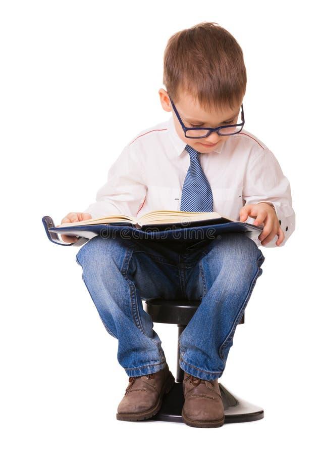 A criança inteligente bonito nos vidros leu o livro de nota imagens de stock