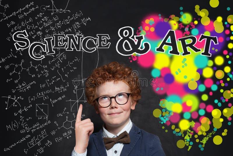Criança inteligente que aponta o dedo na inscrição da ciência e das artes foto de stock royalty free