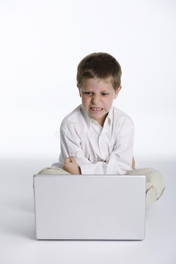 Criança irritada com computador fotografia de stock royalty free