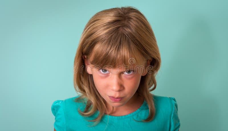 Criança irritada Moça com expressão irritada ou virada na cara no fundo de turquesa Expressão facial da emoção humana negativa fotos de stock royalty free