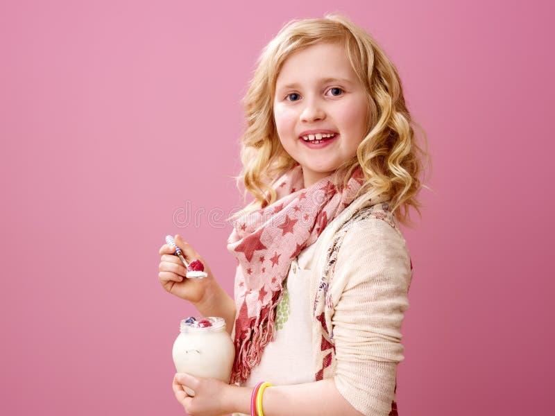 Criança isolada no iogurte orgânico da exploração agrícola cor-de-rosa comer do fundo fotos de stock royalty free