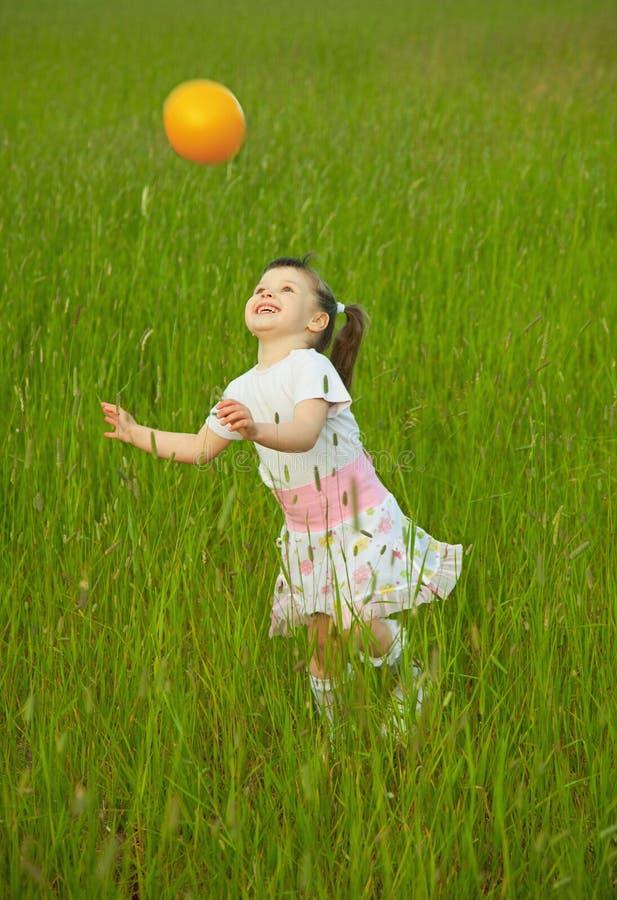 A criança joga alegre com esfera imagens de stock