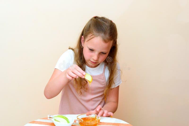 Criança judaica que mergulha fatias da maçã no mel em Rosh HaShanah imagem de stock