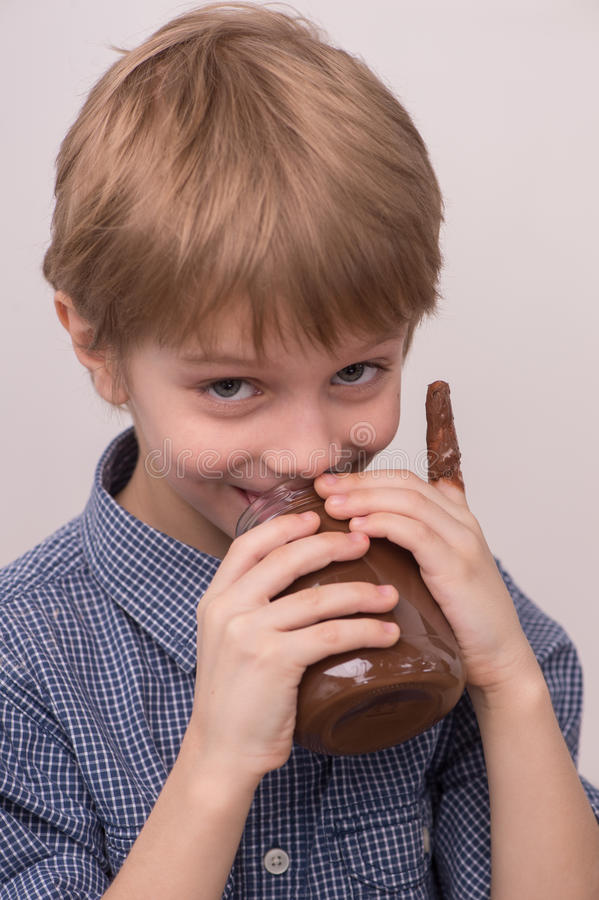 A criança lambe o esmalte do chocolate do frasco foto de stock royalty free
