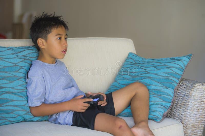 Criança latino 8 anos entusiasmado e jogo de vídeo de jogo feliz velho que guarda em linha o controlador remoto que aprecia tendo imagens de stock