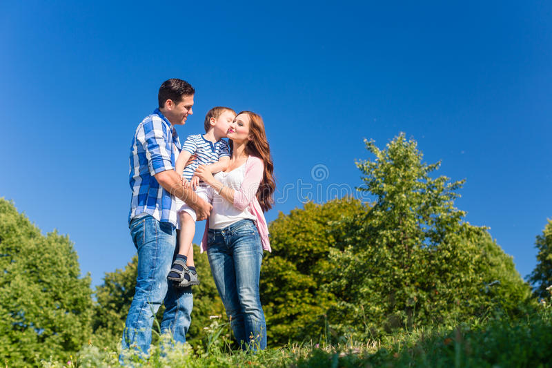 Criança levando da família, pais que estão no prado imagem de stock