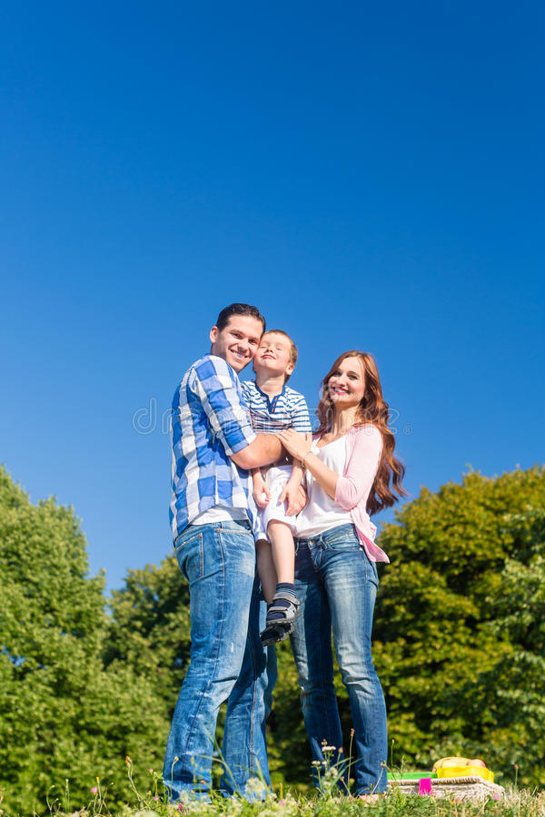 Criança levando da família, pais que estão no prado foto de stock royalty free