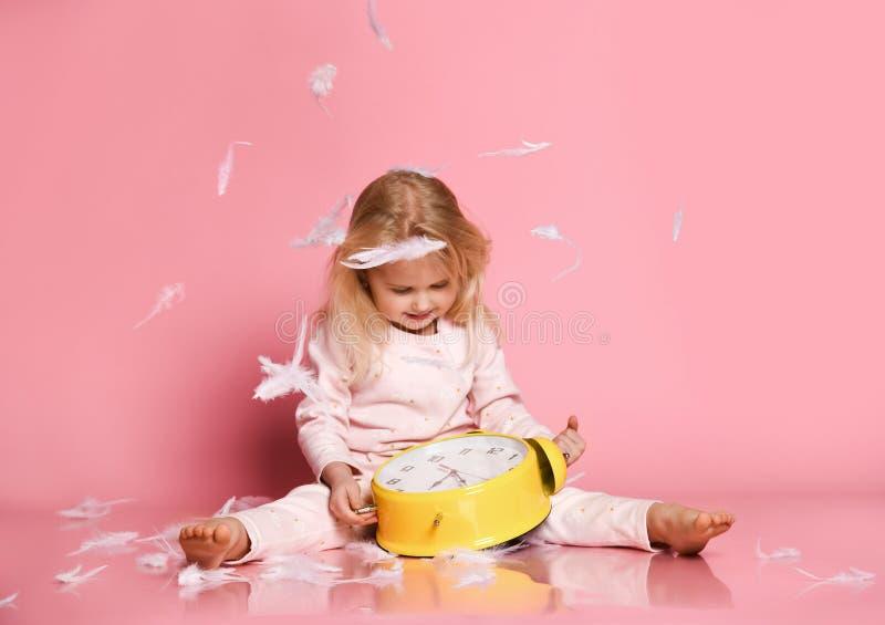 Criança loura bonita que joga com despertador fotografia de stock royalty free