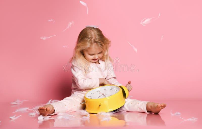 Criança loura bonita que joga com despertador imagens de stock royalty free