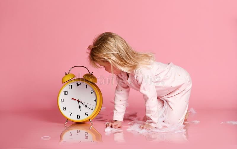 Criança loura bonita que joga com despertador foto de stock royalty free