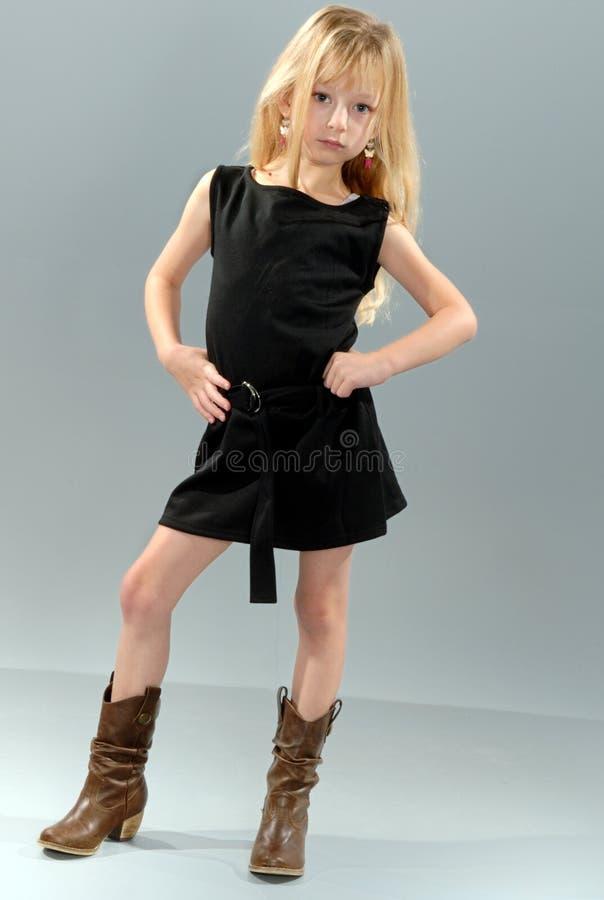 Criança loura bonito no vestido preto imagens de stock royalty free