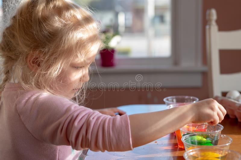 Criança loura bonito que concentra-se ao decorar ovos da páscoa imagens de stock