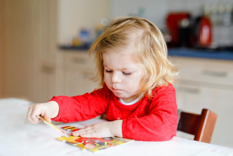 Criança loura da menina pequena adorável da criança, jogando com enigmas em casa ou jardim de infância Criança saudável feliz bon foto de stock royalty free