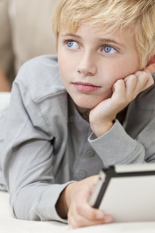 Criança loura do menino dos olhos azuis que usa o computador da tabuleta fotografia de stock royalty free