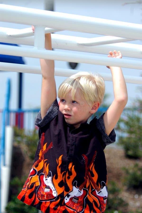 Criança loura do menino em barras imagem de stock royalty free