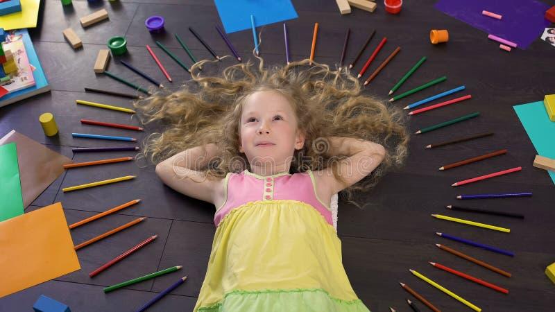 Criança loura encaracolado bonita que encontra-se no assoalho e que sonha sobre presentes fotografia de stock