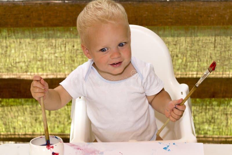 Criança loura entusiasmado com um pincel em suas mãos Pintor pequeno Artista bonito foto de stock royalty free