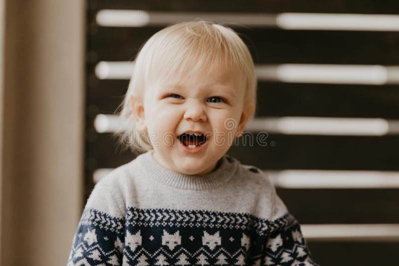 Criança loura pequena adorável bonito da criança que ri, tendo o divertimento, e fazendo as caras parvas fora em casa no patamar  imagem de stock royalty free