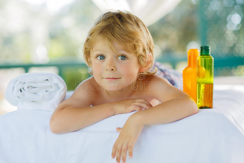 Criança loura pequena adorável que relaxa nos termas com ter a massagem imagem de stock