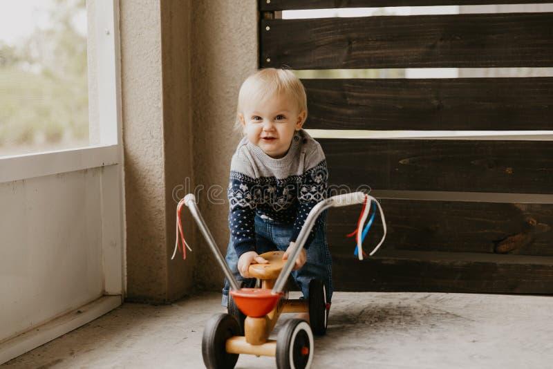 A criança loura pequena bonito adorável preciosa do menino da criança do bebê que joga fora em Toy Bicycle Scooter Mobile Smiling imagens de stock