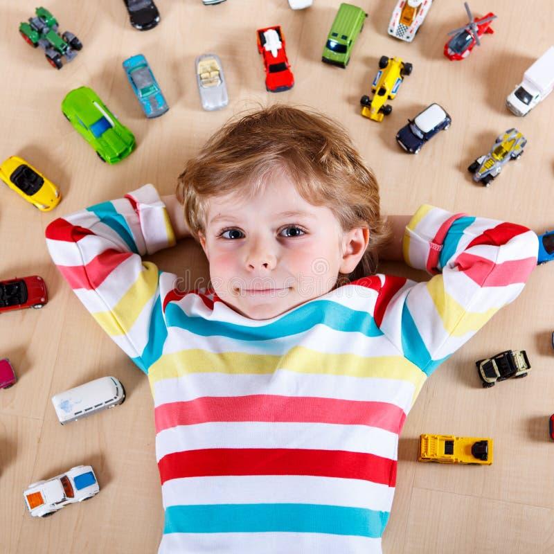 Criança loura pequena que joga com lotes dos carros do brinquedo internos fotografia de stock