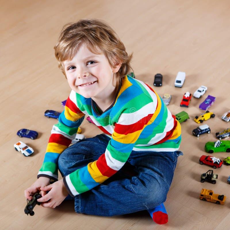 Criança loura pequena que joga com lotes dos carros do brinquedo internos imagens de stock