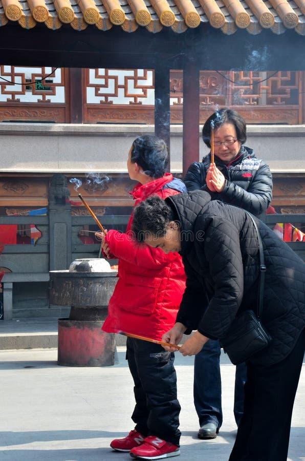 A criança, a mãe e a avó queimam o incenso no templo: Shanghai, China fotografia de stock